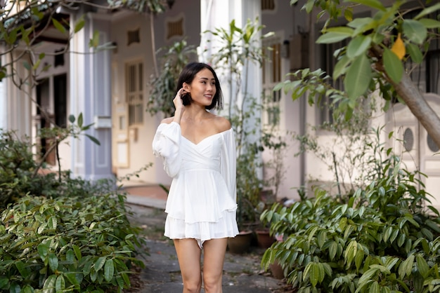 Portrait of beautiful asian woman posing outdoors in a white dress
