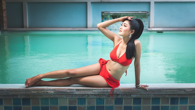Portrait of beautiful asian woman sitting beside swimming pool outdoor with red swimming suit