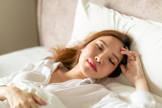 白い枕とベッドで寝ている肖像画の美しいアジアの女性