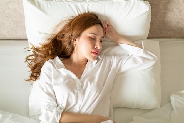 흰색 베개와 함께 침대에서 자고 초상화 아름 다운 아시아 여자