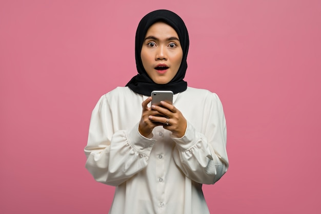 Portrait of beautiful asian woman surprised and holding smartphone