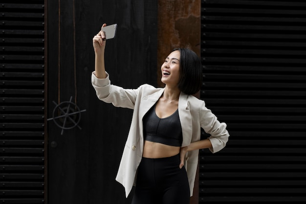 Portrait of beautiful asian woman taking selfie outdoors