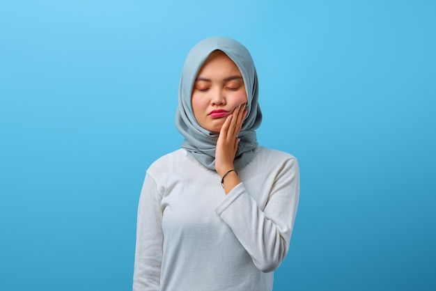Portrait of beautiful asian woman touching mouth with painful expression
