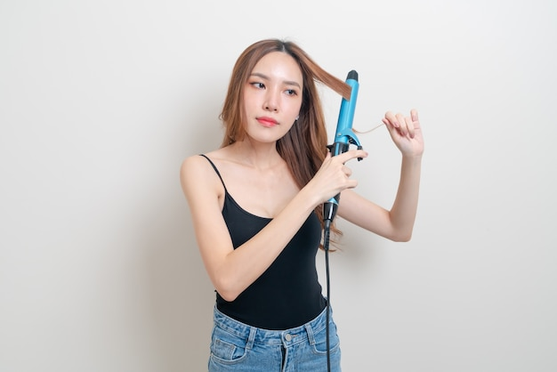 Portrait beautiful asian woman using hair curler or curling iron on white background