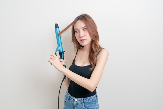 Портрет красивой азиатской женщины с помощью бигуди или щипцов для завивки волос на белом фоне