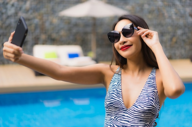 Portrait beautiful asian woman using mobile phone around outdoor swimming pool