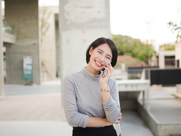 Portrait of beautiful asian woman using mobile phone in young business woman look