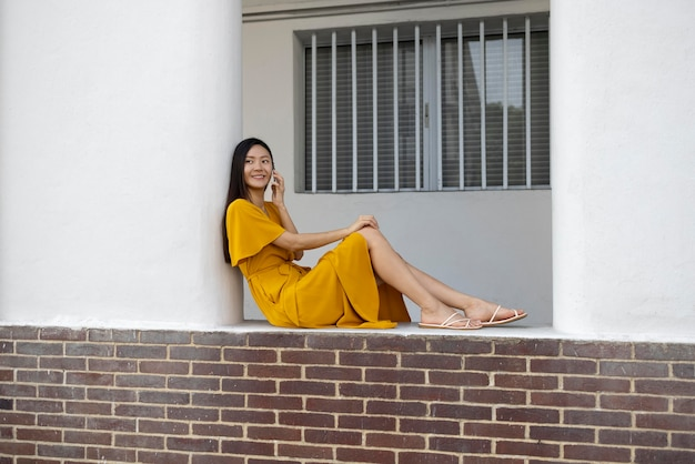 Portrait of beautiful asian woman using smartphone outdoors in the city
