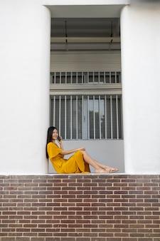 Ritratto di bella donna asiatica che utilizza smartphone all'aperto in città