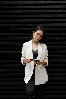 Portrait of beautiful asian woman using smartphone outdoors