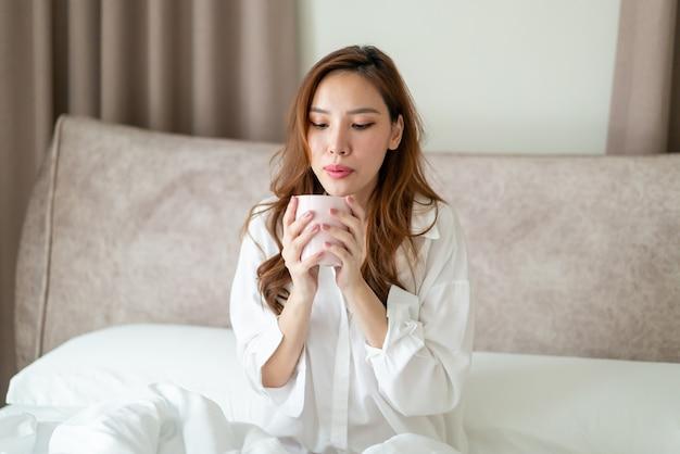 Портрет красивой азиатской женщины просыпается и держит чашку кофе или кружку на кровати утром