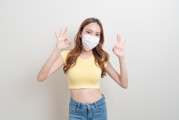 肖像画美しいアジアの女性は、okまたは白い背景の上の手のサインに同意するマスクを身に着けています