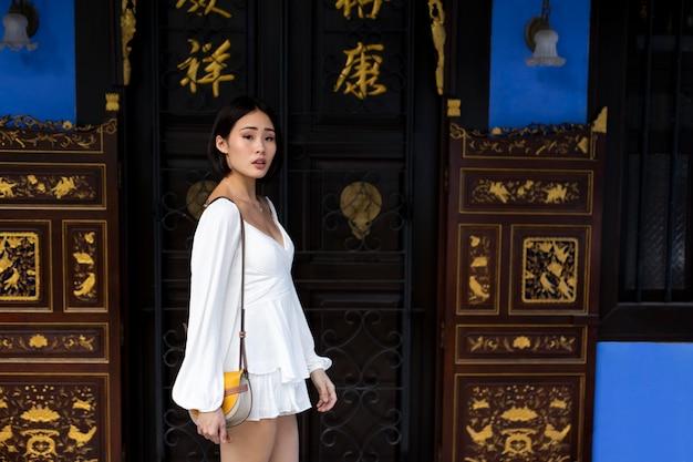 Ritratto di bella donna asiatica in abito bianco all'aperto in città
