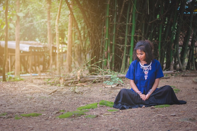 Portrait of beautiful asian woman with local dress, sitting under bamboo tree with peace in mind, in