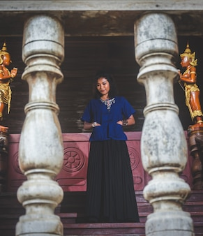 Portrait of beautiful asian woman with local dress, standing in public temple at countryside of thai