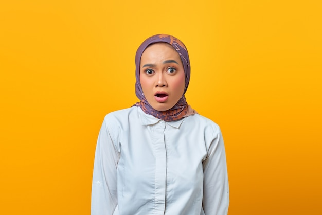 Portrait of beautiful asian woman with shocked expression over yellow background