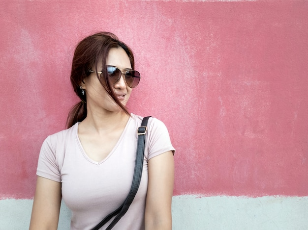Portrait of beautiful asian woman with sunglasses in a city over pink wall background
