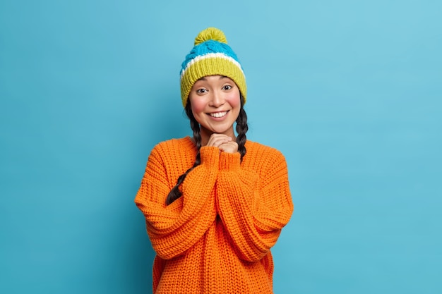 Ritratto di bella donna asiatica con sorriso a trentadue denti tiene le mani unite essendo di buon umore indossa cappello lavorato a maglia invernale e maglione arancione pone contro il muro blu