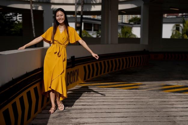 Ritratto di bella donna asiatica in vestito giallo che posa all'aperto nella città