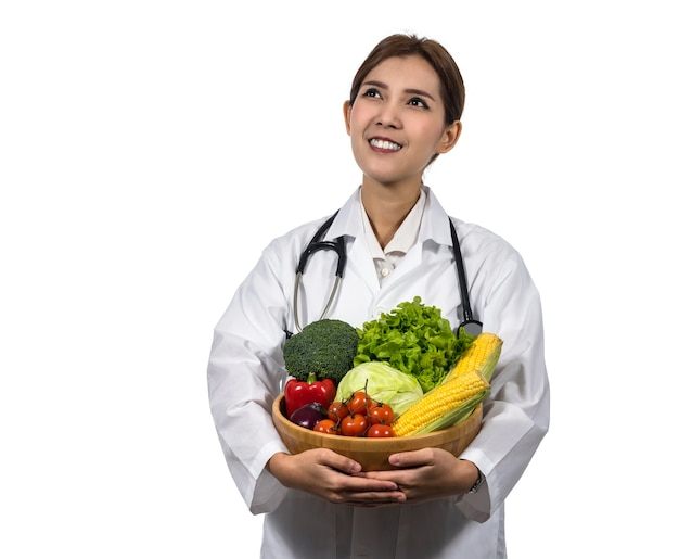 Portrait of beautiful asian young doctor holding the mix fresh vegetables in wooden bowl
