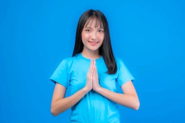 Portrait beautiful asian young woman bangs hair style pay respect , sawasdee symbol from thailand greeting culture for hello or goodbye isolated on blue background