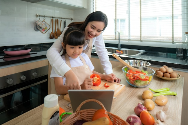 Portrait of beautiful asian young woman and her daughter cooking salad for lunch using online internet in a digital tablet search recipe while making food,