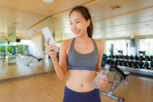 Молодая женщина портрета красивая азиатская используя мобильный телефон в спортзале