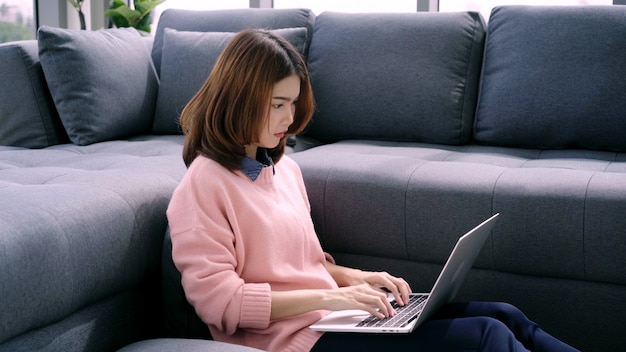 Portrait of beautiful attractive young smiling asian woman using computer or laptop while lying on the sofa