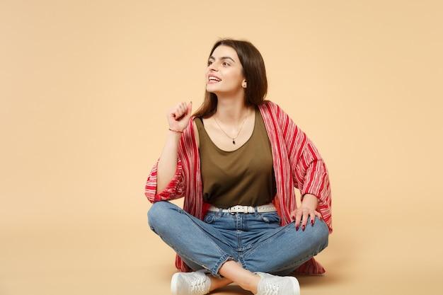 Ritratto di bella giovane donna attraente in vestiti casuali che si siede guardando da parte isolato sul fondo beige pastello della parete in studio. persone sincere emozioni, concetto di stile di vita. mock up copia spazio.