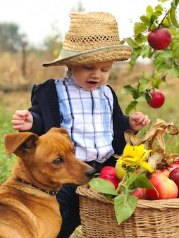 Portrait of beautiful baby boy eating apple on the lawn