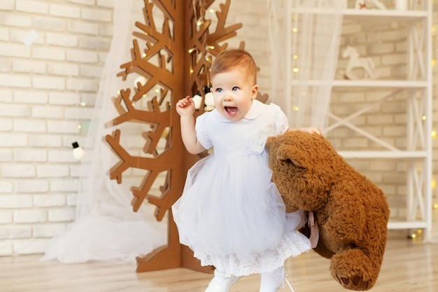 Portrait of a beautiful baby girl with a soft brown teddy bear in the interior with christmas decorations.