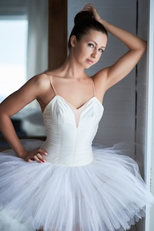 Portrait of beautiful ballerina posing next to window and looking at camera. copyspace