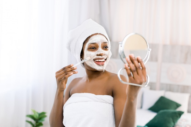 Portrait of beautiful black african model with a facial face mask holding a mirror, rejuvenating skin care regime treatment beauty concept