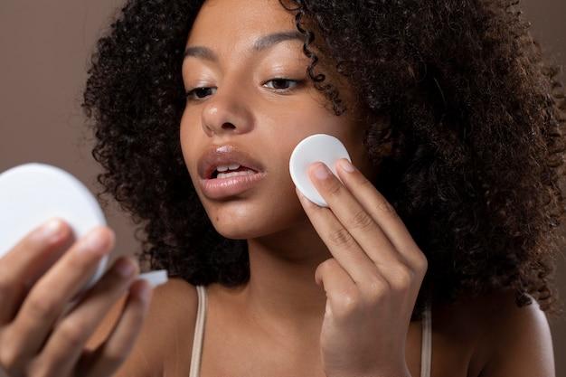 Ritratto di bella donna di colore che fa la sua routine di cura della pelle