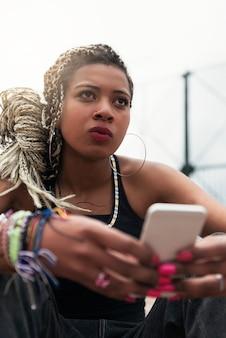 Portrait of beautiful black woman using her mobile in her neighborhood. slum concept.