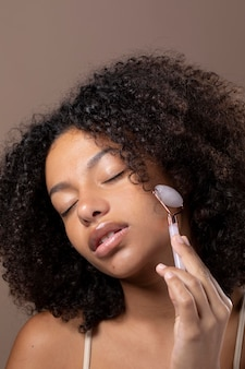 Portrait of beautiful black woman using a jade roller on her face