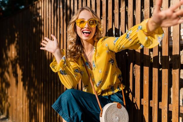 Ritratto di bella donna sorridente alla moda che ride emotiva bionda in camicetta gialla che indossa occhiali da sole, borsa di paglia stile bali