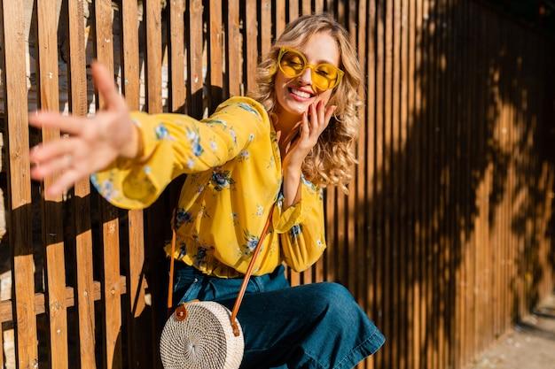 Ritratto di bella donna sorridente alla moda che ride emotiva bionda in camicetta gialla che indossa occhiali da sole, borsa di paglia stile bali Foto Gratuite
