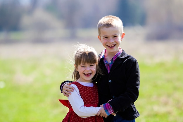 Portrait of beautiful blond smiling children with funny child teeth in smart clothes