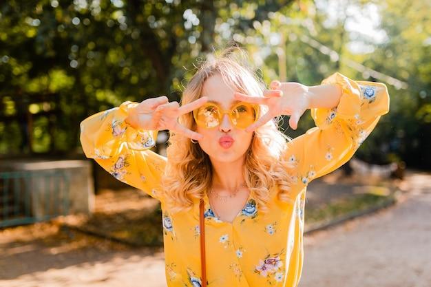 Ritratto di bella donna emotiva alla moda bionda in camicetta gialla che indossa occhiali da sole, divertente espressione del viso pazzo