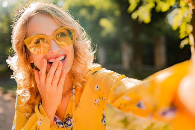 Portrait of beautiful blond stylish  smiling woman in yellow blouse wearing sunglasses making selfie photo