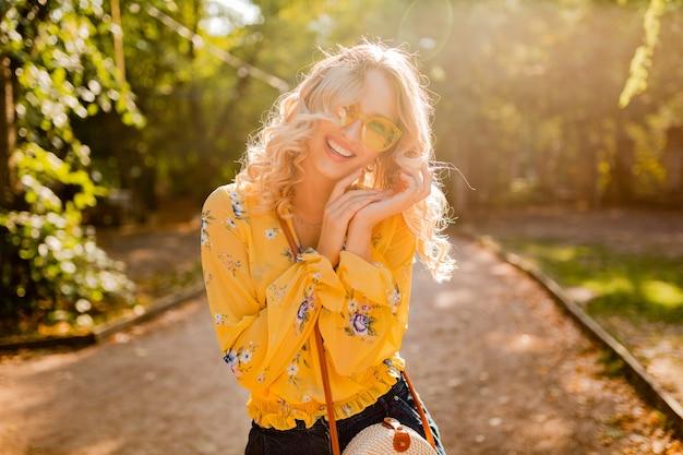 Ritratto di bella donna sorridente alla moda bionda in occhiali da sole da portare della camicetta gialla