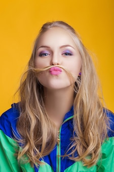 Portrait of beautiful blond woman in casual colorful vivid clothes making mustache with her hair