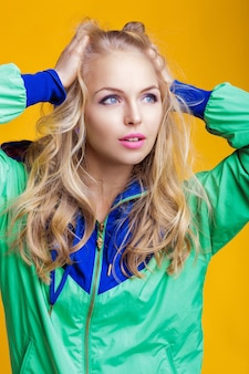 Portrait of beautiful blond woman in casual colorful vivid green summer clothes on yellow background