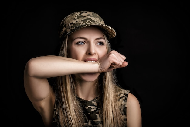 Portrait of a beautiful blond woman soldiers in military attire on black background. fear and hunger