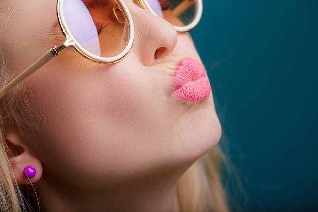 Portrait of beautiful blond woman in sunglasses on blue background carefree summer close up