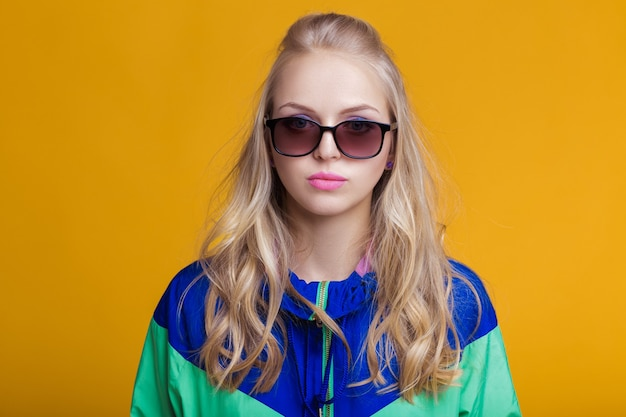 Portrait of beautiful blond woman in sunglasses and blue green hooded jacket on yellow background hi...