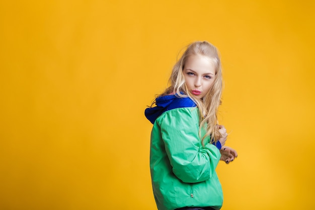 Portrait of beautiful blond woman in sunglasses and blue green jacket on yellow background hipster s...