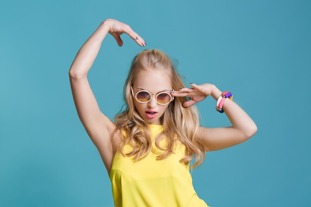 Portrait of beautiful blond woman in sunglasses and yellow shirt on blue background carefree summer