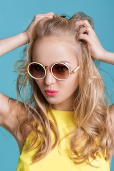 Portrait of beautiful blond woman in sunglasses and yellow shirt on blue carefree summer
